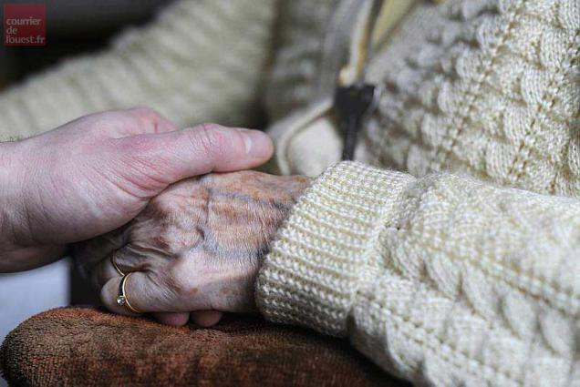 A woman, suffering from Alzheimer's desease, holds the hand of a relative on March 18, 2011 in a retirement house in Angervilliers, eastern France.   AFP PHOTO / SEBASTIEN BOZON