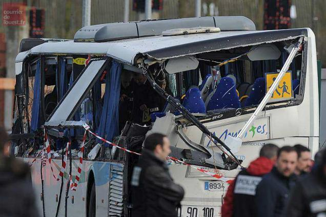 French police work in the wreckage of a school bus after it crashed into a truck in Rochefort on February 11, 2016, killing at least six children, police said, a day after another road accident involving a school bus left two youngsters dead. The head-on smash with a lorry carrying rubble came around 7:15 am (0615 GMT) in Rochefort in the western Charente-Maritime region. / AFP / XAVIER LEOTY