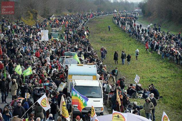 French protesters march on a highway in Le Temple-de-Bretagne during a demonstration against a controversial airport project near Nantes on February 27, 2016. Protesters have been engaged in a 15-year legal battle to block the construction of a major new airport on swampland outside the western city of Nantes. Approved in 2008, the 580-million-euro (747 million USD) project had been due to start in 2014 but has been repeatedly delayed due to fierce opposition by environmental protesters.  / AFP / JEAN-SEBASTIEN EVRARD